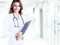 Smiling medical doctor woman with a folder in hospital on background of bright hall royalty free stock photo