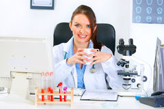 Smiling medical doctor woman holding cup in hands Royalty Free Stock Photo