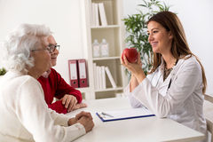 Smiling medical doctor woman offering apple to senior couple Stock Image