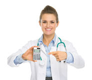 Smiling medical doctor woman pointing calculator Royalty Free Stock Images