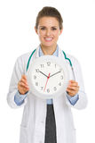 Smiling medical doctor woman showing clock. Isolated on white Royalty Free Stock Images