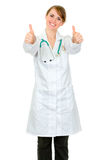 Smiling medical doctor woman showing thumbs up Stock Photo