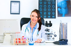 Smiling medical doctor woman sitting at table Royalty Free Stock Image