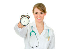 Smiling medical female doctor holding alarm clock Royalty Free Stock Photo