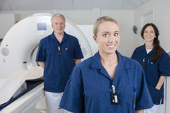Smiling Medical Professional With Colleagues Standing By MRI Mac Stock Photo