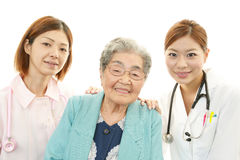 Smiling medical staff with old woman Stock Images