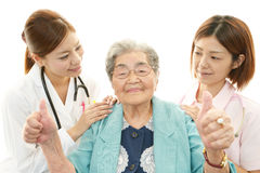 Smiling medical staff with old woman Royalty Free Stock Image
