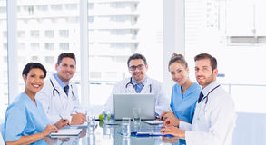 Smiling medical team around desk in office Royalty Free Stock Photo
