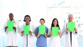 Smiling medical team showing blank papers Stock Image