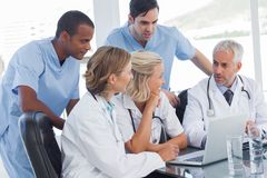Smiling medical team using laptop Royalty Free Stock Photos