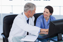 Smiling medical team working with a computer Royalty Free Stock Photo