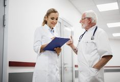 Smiling medical workers chatting in hospital hallway. Waist up portrait of old doctor with stethoscope talking with lovely nurse in white lab coat while she stock photography