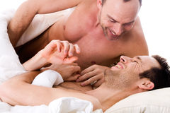 Smiling men couple in bed royalty free stock photography