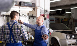 Smiling men in coveralls working. Cheerful two male workers in overalls working in the garage Royalty Free Stock Image