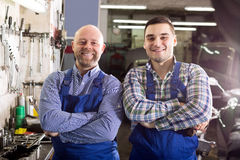 Smiling men in coveralls working Stock Photography