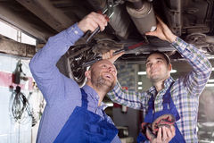 Smiling men in coveralls working. Happy two male workers in overalls working in the garage. Focus on the left man Stock Images