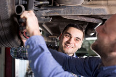 Smiling men in coveralls working Stock Image