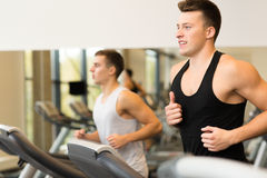 Smiling men exercising on treadmill in gym Royalty Free Stock Photography