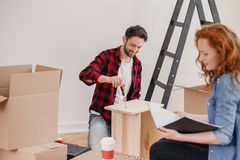 Smiling man folding furniture while woman unpacking stuff after relocation. Smiling men folding furniture while women unpacking stuff after relocation concept stock photography