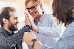 close-up view of cheerful middle aged men giving high five stock photo