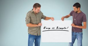 Smiling men holding billboard with keep it simple text against blue background Royalty Free Stock Image