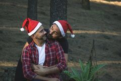 Romantic scene of young gay couple with red Christmas hats in forest park