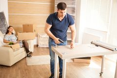 Smiling man putting together self assembly furniture in new home. Smiling men putting together self assembly furniture in new home. Furniture in new house stock image