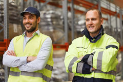 Smiling men in reflective uniform at warehouse Royalty Free Stock Photography