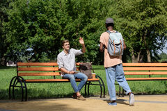 Man sitting on bench and waving to friend in park Stock Image
