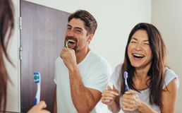 Smiling couple brushing teeth in bathroom stock photos