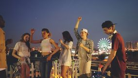 Smiling men and women are dancing at roof party celebrating holiday when deejay is working with digital mixing console