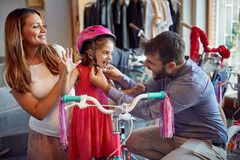 Smiling man and woman shopping new bicycle and helmets for little girl in bike shop. Smiling men and women shopping new bicycle and helmets for happy little girl royalty free stock images