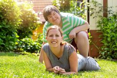 Smiling mental disabled woman and a friend in the garden royalty free stock photography