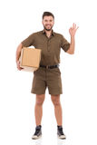 Smiling Messenger Is Holding Box Under His Arm And Showing Ok Sign. Smiling delivery man in khaki uniform is standing, holding carton box under the arm and Stock Images