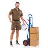 Smiling Messenger Is Standing Close To A Push Cart Royalty Free Stock Photography