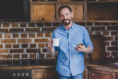 Man holding coffee cup. Smiling mid adult man holding coffee cup and listening music on smartphone at the kitchen Stock Photos