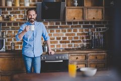 Man holding coffee cup. Smiling mid adult man holding coffee cup and looking at the camera at the kitchen Royalty Free Stock Photo