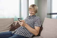 Smiling mid-adult man text messaging on sofa at home Royalty Free Stock Photo