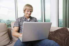 Smiling mid-adult man using laptop on sofa at home Royalty Free Stock Photos