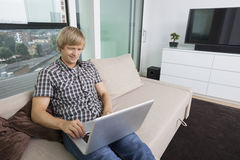 Smiling mid-adult man using laptop on sofa at home Stock Photos