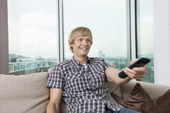 Smiling mid-adult man watching television on sofa at home Stock Images