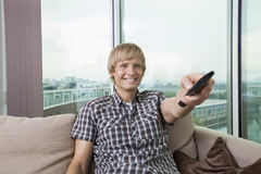 Smiling mid-adult man watching television on sofa at home Stock Image