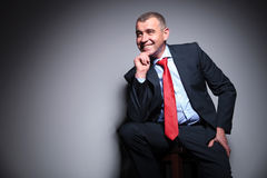 Smiling mid aged business man sitting on a stool. Holding his hand to the chin, looking away Stock Photos