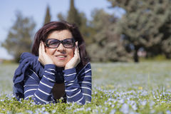 Mid aged woman relaxing on grass Stock Photo