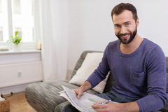 Smiling Middle Age Man Holding Newspaper and Pen Stock Image