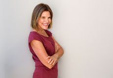 Smiling middle age woman against white wall Royalty Free Stock Photos