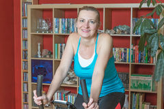 Smiling middle age woman on the exercise bike. Indoors Royalty Free Stock Photography