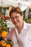 Smiling middle age woman at grocery market royalty free stock photography