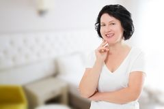 Smiling middle age woman at home . Skin care and dental medicine for white teeth. Blur background with copy space stock images