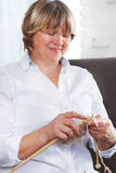 Smiling middle age woman knitting on spokes at home Royalty Free Stock Photo